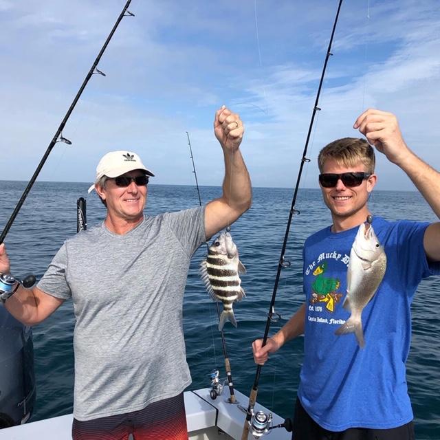 Two men holding fish